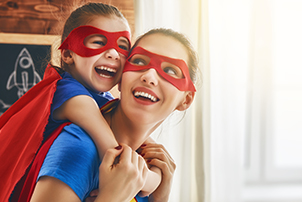 A foster mum and girl dressed like super heroes