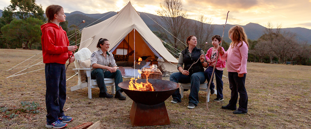 A family sits by a fire roasting marshmallows at Wildfest.