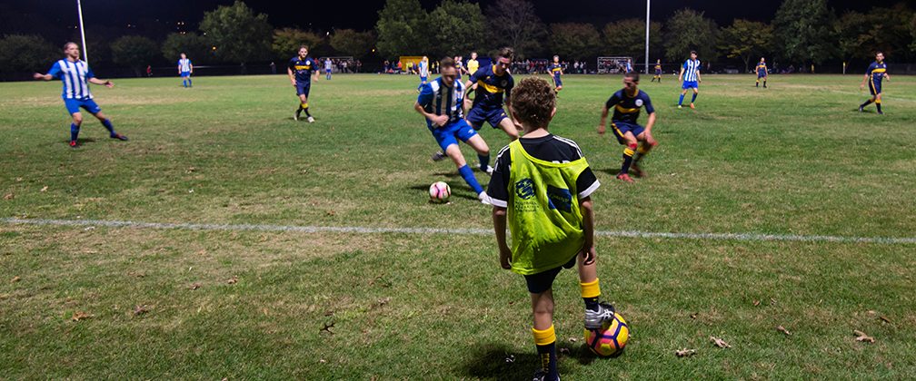 A young soccer player watches a soccer match at Calwell Oval.