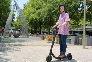 A man riding an e-scooter in Canberra City.