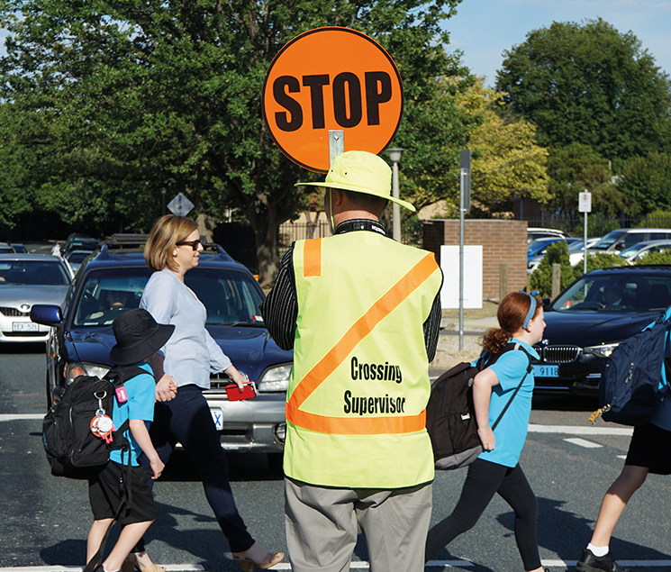School children crossing the road with assistance from a School Crossing Supervisor.