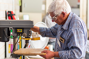 A man using some of the tools on offer at the Weston Creek Men's Shed.