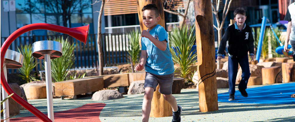 Two young boys running in the Gungahlin Place play space