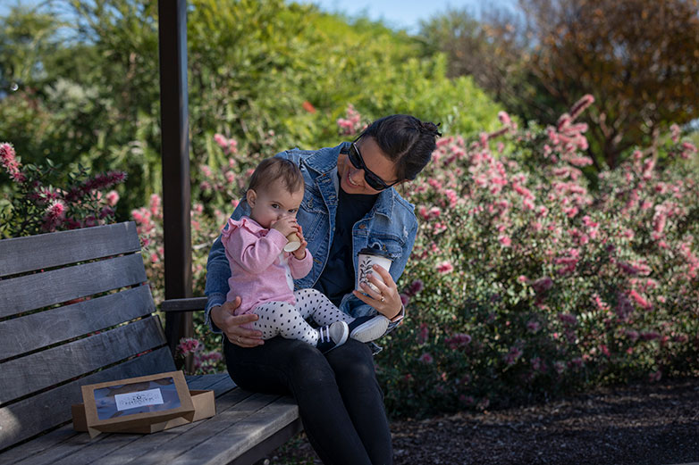 Image of a woman and baby sitting on a bench