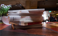 A pile of academic books on a table