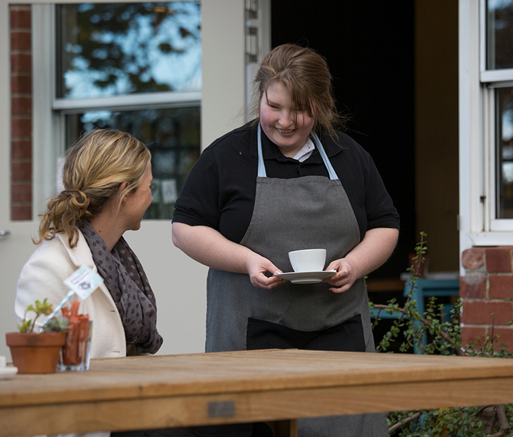 Student serves coffee to a customer at Six Degrees cafe