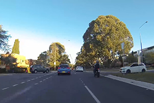 A motorcycle and cars sharing the road safely.