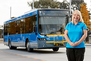 A Transport Canberra bus driver, standing in front of her bus.
