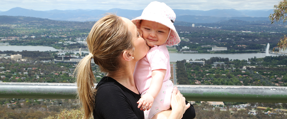 A mother holding her baby on top of Mt Ainslie in Canberra