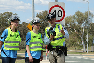 High school students with a Police Officer standing in front of a school speed zone sign