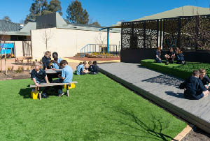 Primary school children sitting in a grassy courtyard interacting with each other