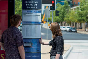 Man and woman looking at bus stop timetable.