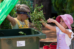 Children using their green bin to dispose of garden clippings.