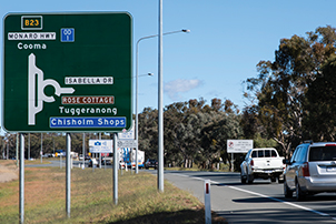 Cars driving along the Monaro Highway near a street sign.