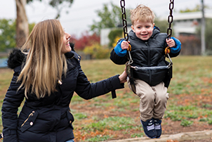 A boy on a swing at a playground with his mother.