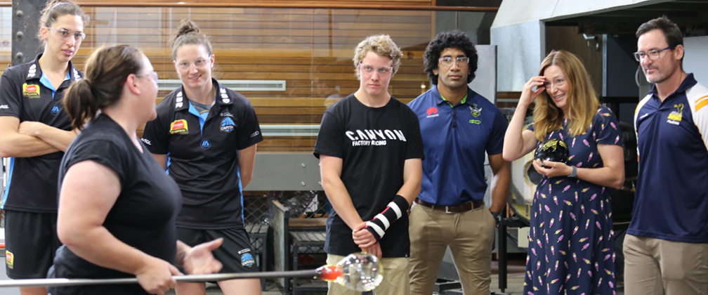 Annette Blair glass demonstrating with Marianna Tolo (UC Capitals), Kelsey Griffin (UC Capitals), Kye A'Hern (Downhill Moutain Biking), Sia Soliola (Canberra Raiders), Yvette Berry MLA and Dan McKellar (Brumbies Rugby).
