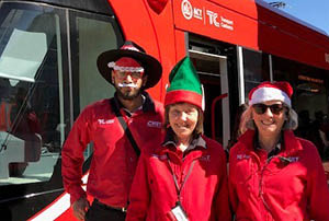 Three light rail customer service officers dressed in Christmas gear standing in front of a light rail vehicle.