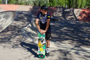 Ethan Copeland standing with his skateboard in a skate park in Woden.