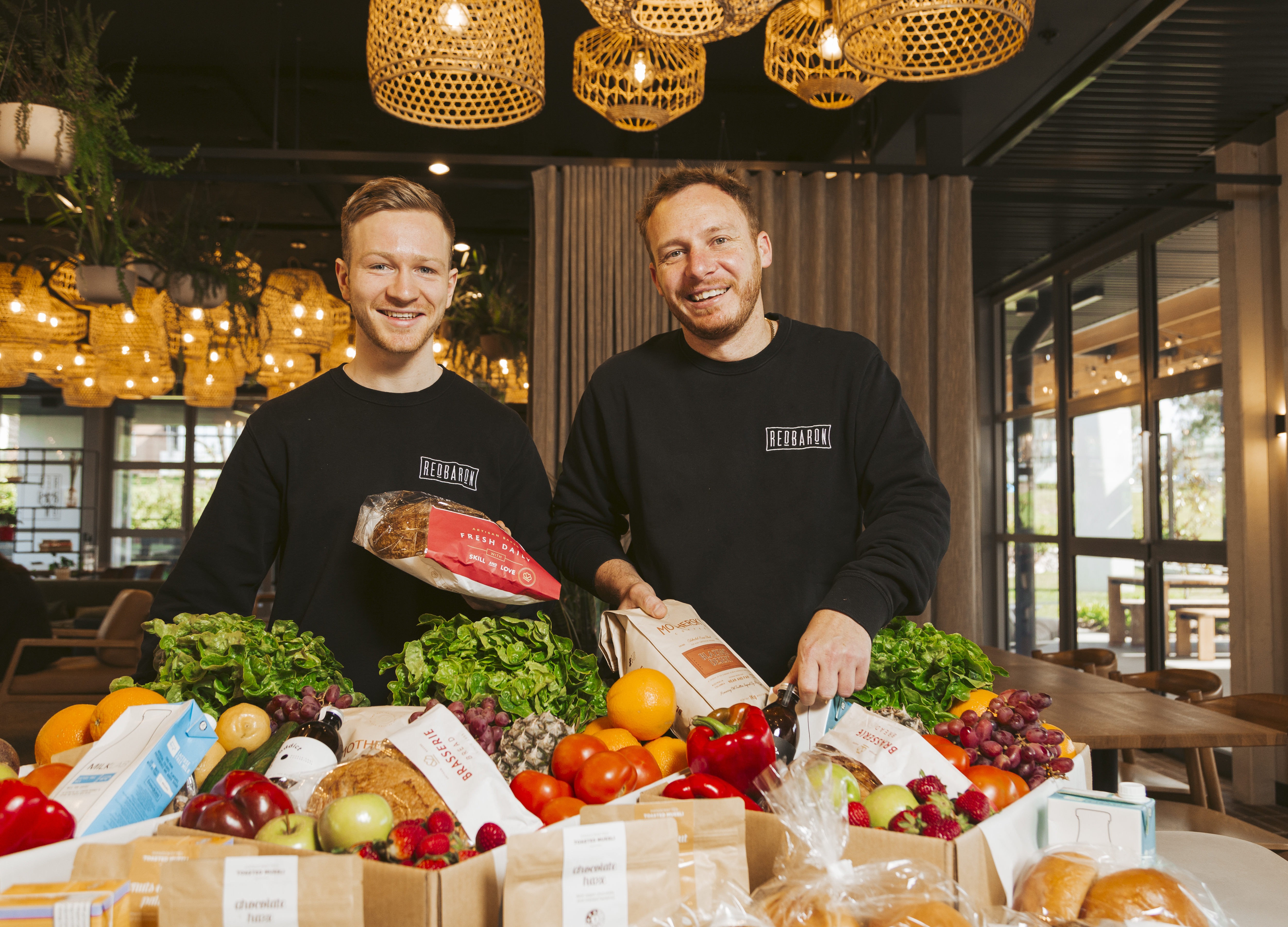 Two men standing behind boxes of fresh produce.