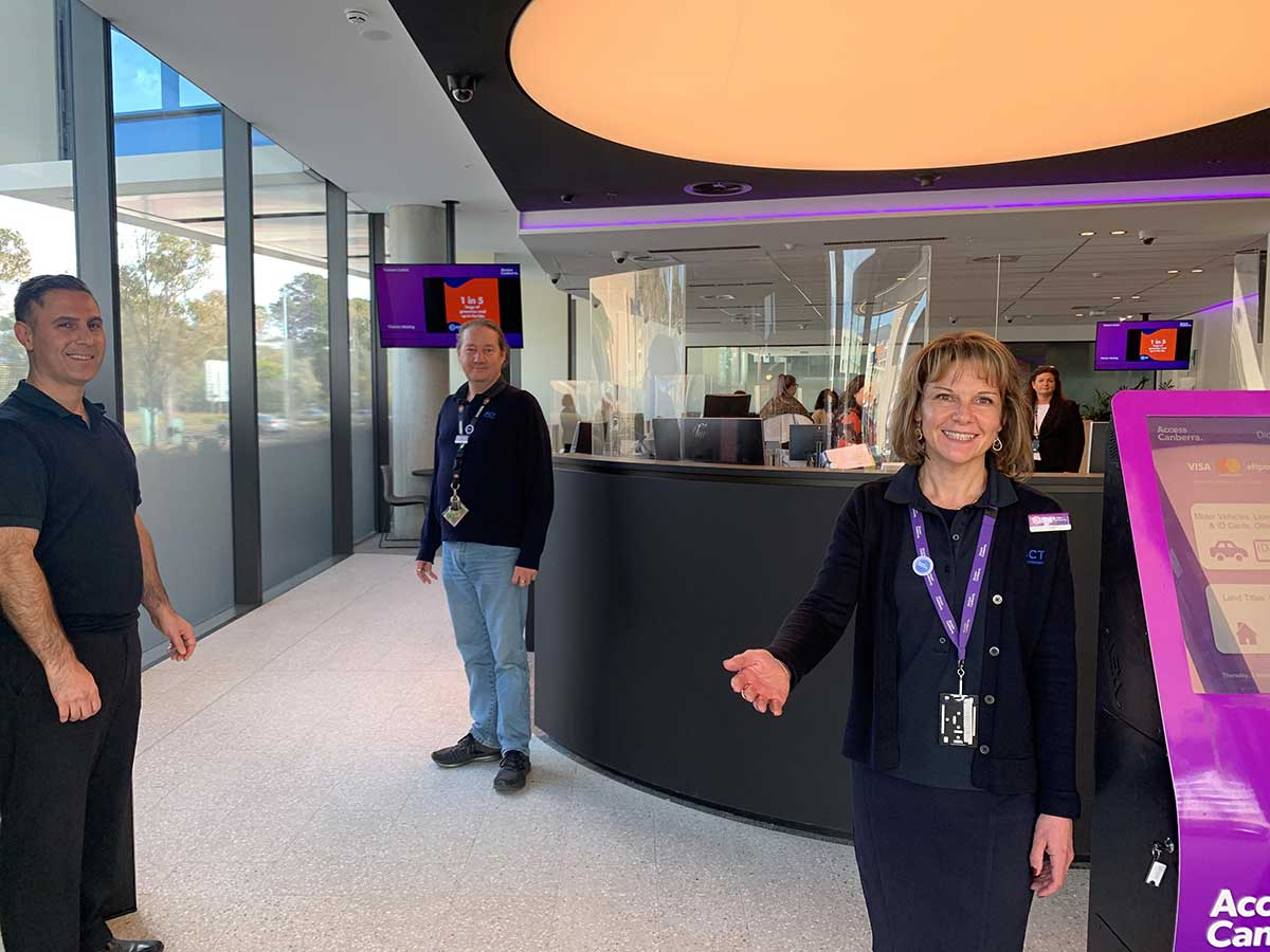 A woman and two men stand inside a modern new service centre.