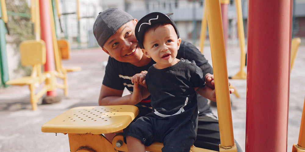 A father and son play at a park