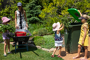 A woman and children putting garden waste in a green bin