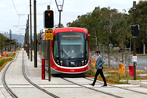 A pedestrian walking across the light rail track at a designated crossing.