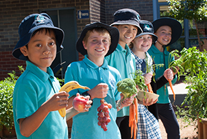 School students holding fruit and vegetables.