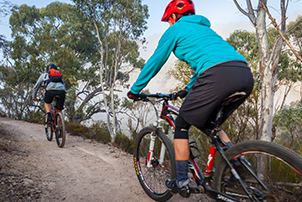 Two people cycling on a dirt path in Namadgi National Park.