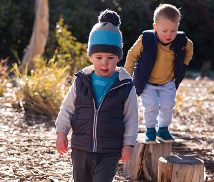 Two young boys playing at a natural play area in Canberra