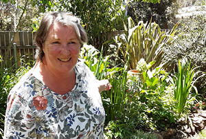 Winner Jenny Stevens from Macquarie standing in front of her garden.