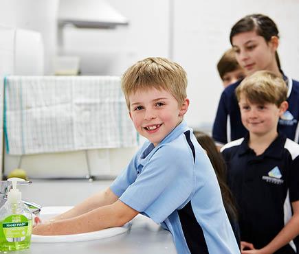 School children lining up to wash hands.