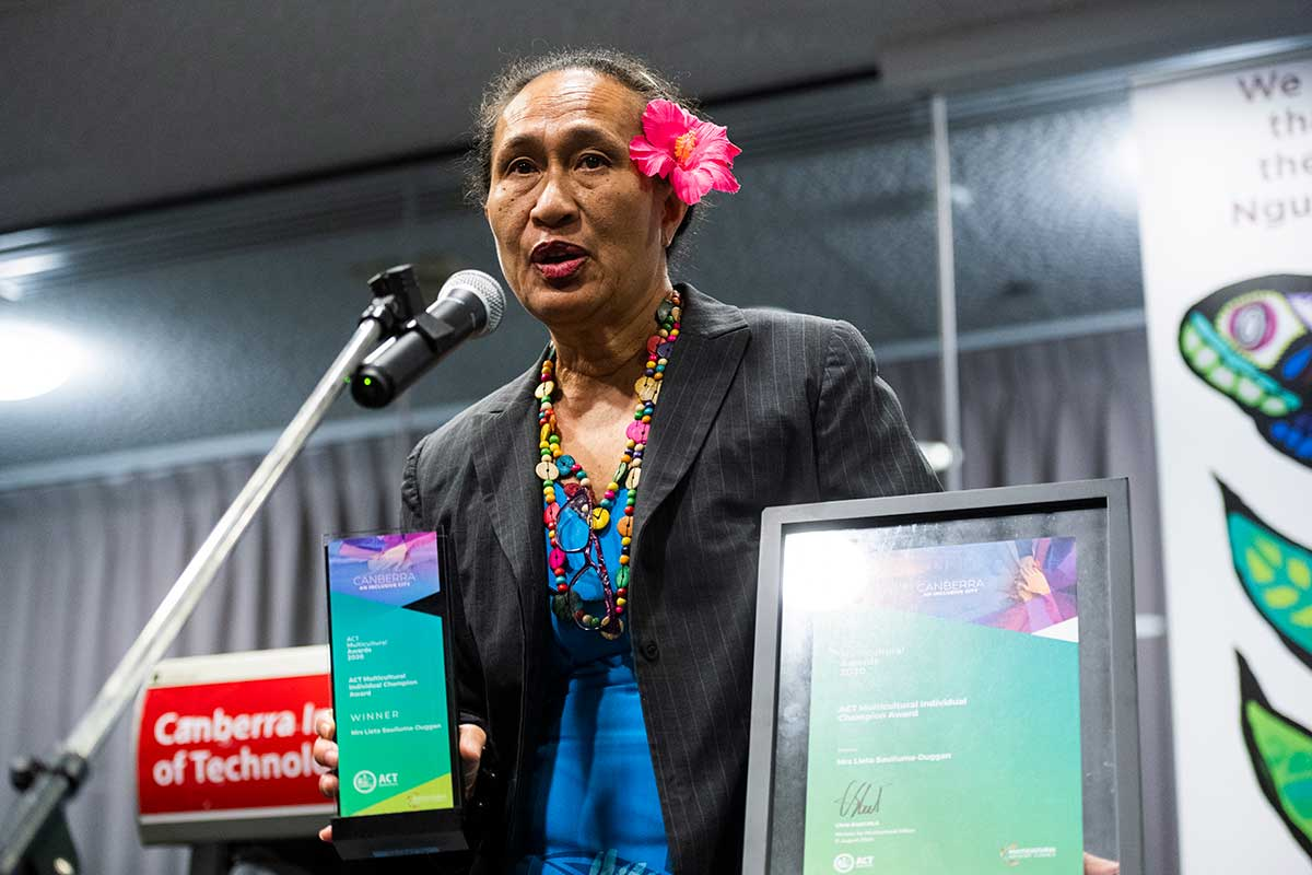Woman accepting award and talking into microphone.