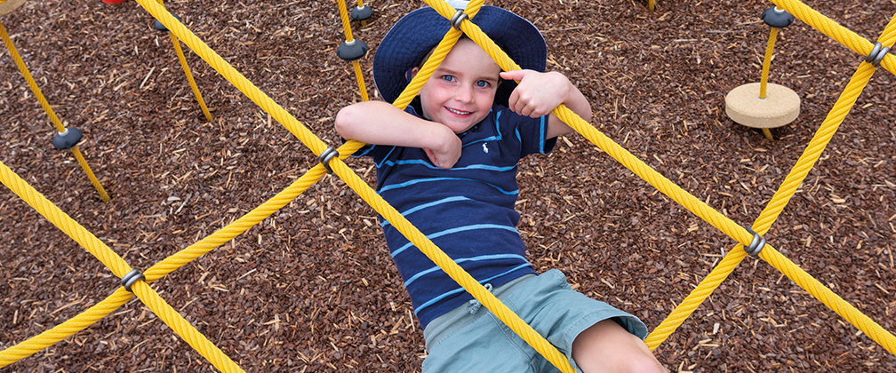 A child hangs upside down on a climbing frame at the new Taylor playground.