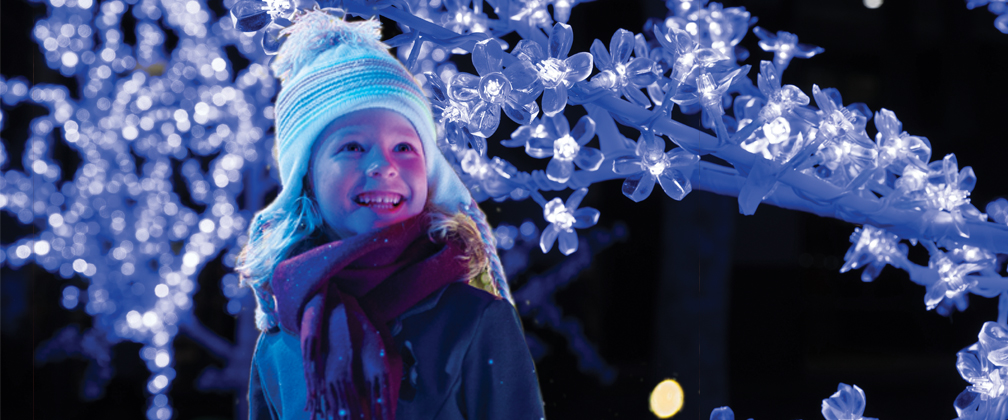 A young girl in winter clothes standing in front of fairy lights at night.