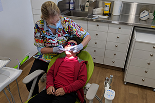 A dentist assessing a child in the dental chair.