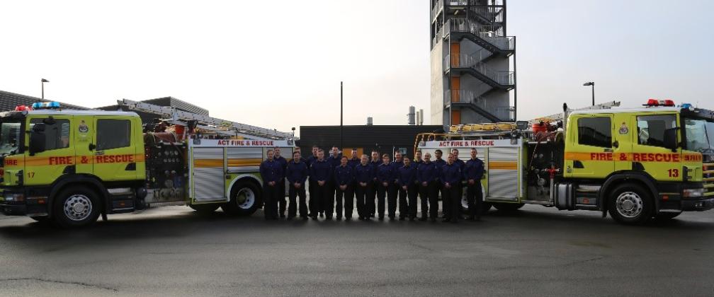 20 new firefighters standing between two fire trucks.