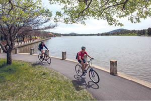Two cyclists ridding along Lake Tuggeranong.