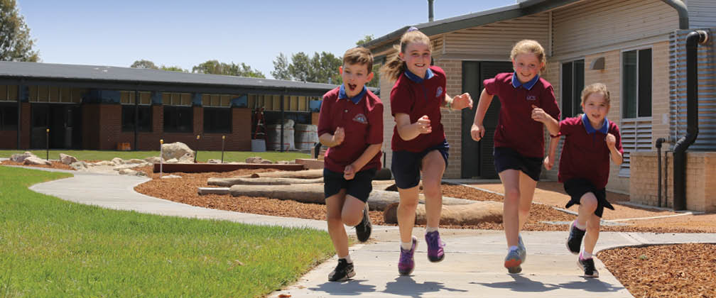 Four children running at a school.