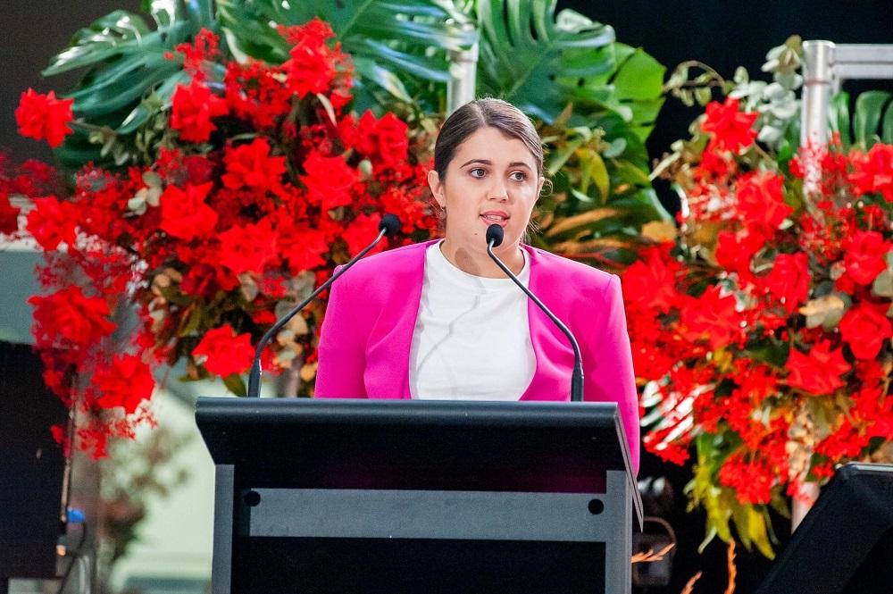 Tara McClelland stands at a lectern giving a speech