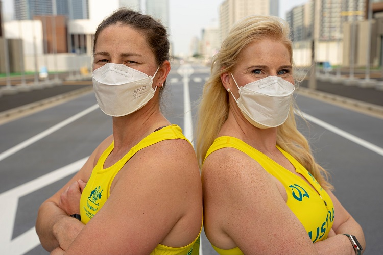 Two women stand back to back with their arms folded across their chests wearing surgical masks and their Australian Paralympic uniform