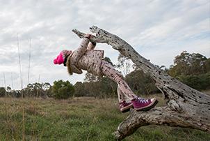 Girl playing on fallen tree stump