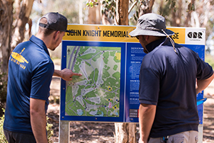 People playing Disc Golf at John Knight Memorial Park.