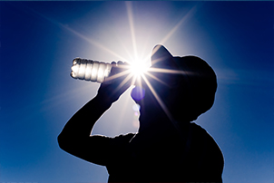 Man drinking water in the heat.