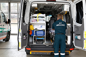 An ambulance officer working in the back of an ambulance in an Emergency station in Canberra.