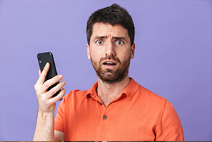 Man holding phone and looking confused