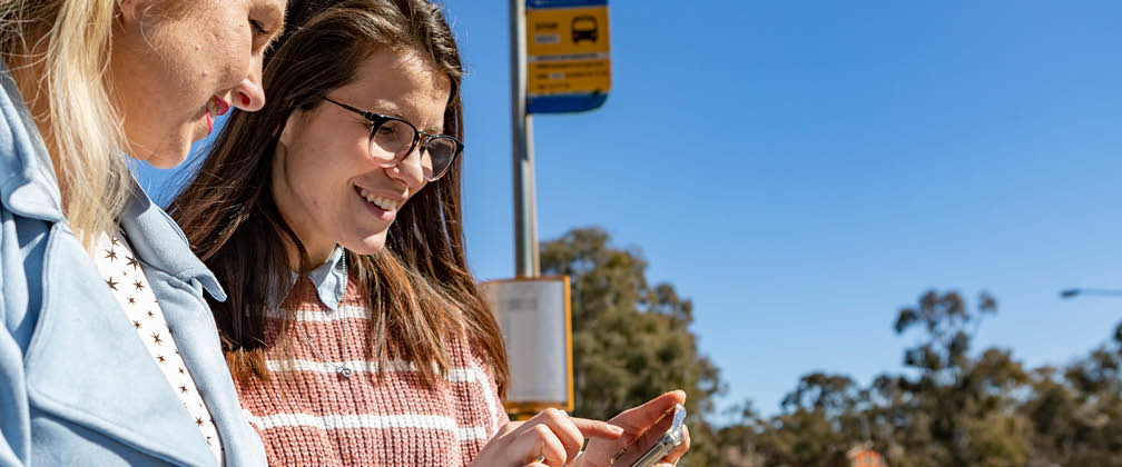 Two women at a bus stop looking at a phone.