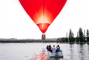 Boat on a lake under heart-shaped hot air balloon.