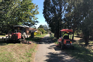 Two ride-on lawnmowers working next to a footpath.