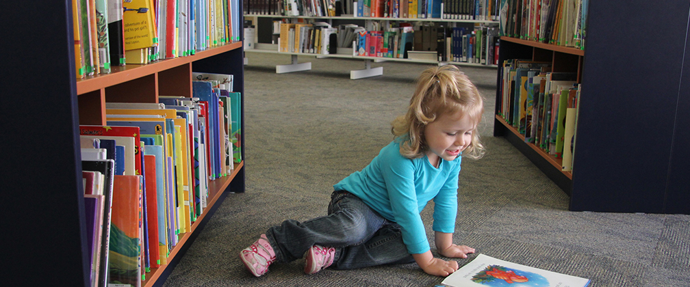 Little girl reading at library